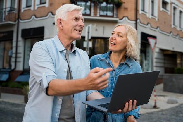 Casal de idosos fora da cidade, segurando um laptop