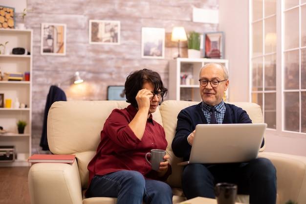 Casal de idosos idosos usando laptop moderno para conversar com seu neto. avó e avô usando tecnologia moderna