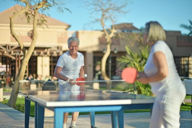 Casal de idosos jogando pingue-pongue no quintal do hotel