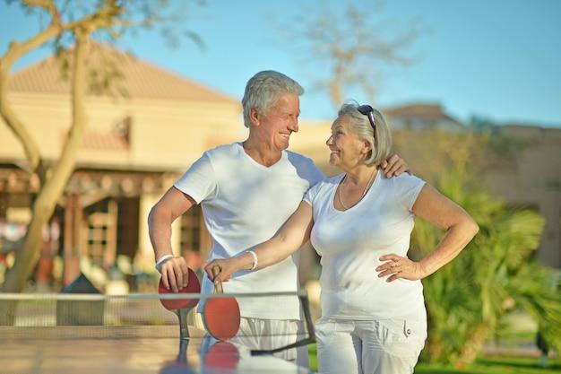 Casal de idosos jogando pingue-pongue no quintal do hotel Foto Premium