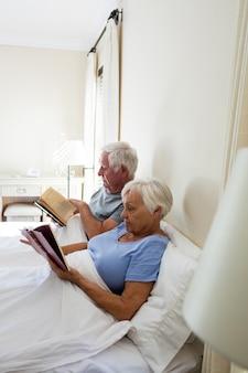 Casal de idosos lendo livros no quarto de casa