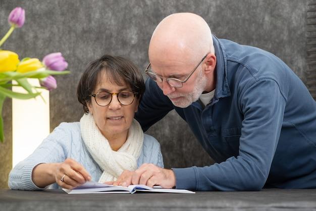 Casal de idosos lendo um livro em casa