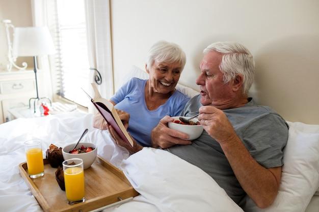 Casal de idosos lendo um livro enquanto toma o café da manhã no quarto de casa