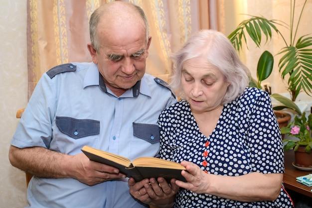 Casal de idosos lendo um livro juntos em casa