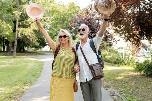 Casal de idosos levantando seus chapéus no ar