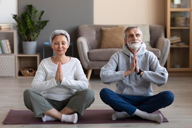 Casal de idosos meditando em casa