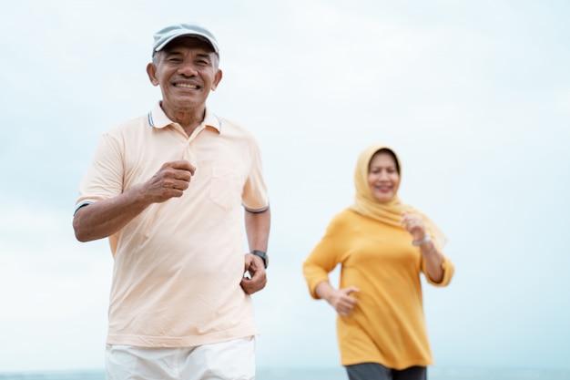 Casal de idosos muçulmanos treino e correndo na praia