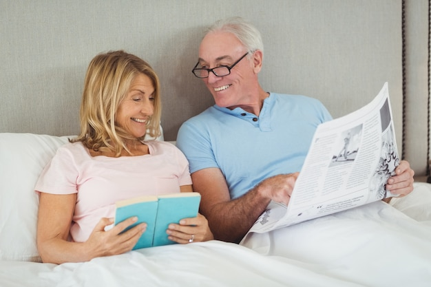 Casal de idosos na cama lendo jornal e livro