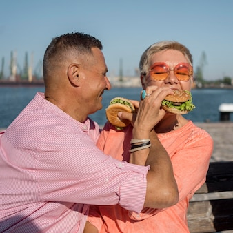 Casal de idosos na praia comendo hambúrgueres
