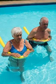 Casal de idosos nadando na piscina com tubos infláveis em um dia ensolarado