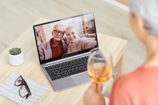Casal de idosos no monitor do laptop sorrindo e conversando com um amigo que está sentado em casa bebendo vinho