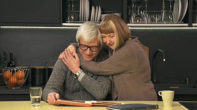 Casal de idosos olhando para um álbum de fotos antigo e sorrindo