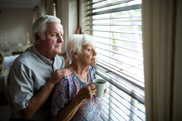 Casal de idosos olhando pela janela de casa
