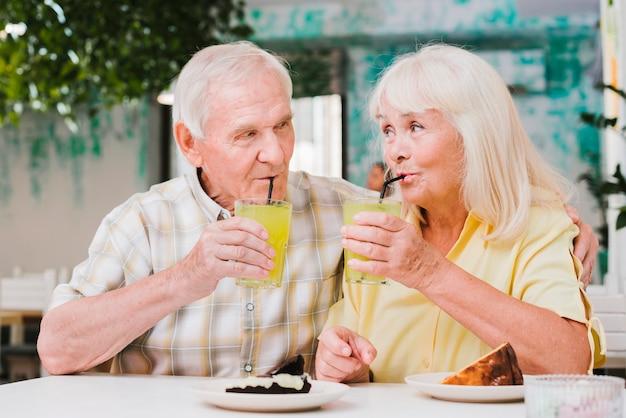 Casal de idosos positivos abraçando no café, apreciando a bebida refrescante e sobremesa