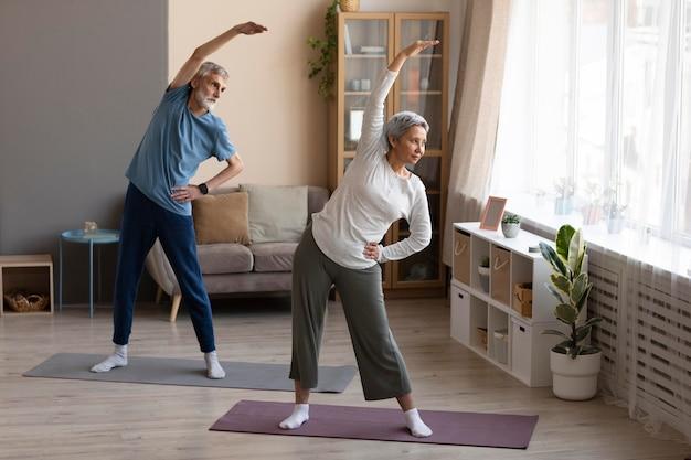 Casal de idosos praticando ioga em casa