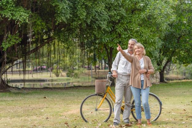 Casal de idosos relaxando após andar de bicicleta no parque