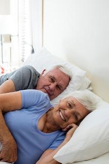 Casal de idosos relaxando no quarto em casa
