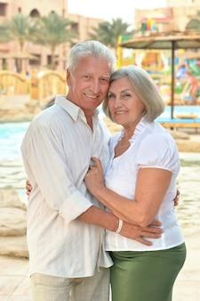 Casal de idosos relaxando perto da piscina em hotel resort