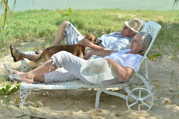 Casal de idosos relaxando perto de hotel resort com cachorro