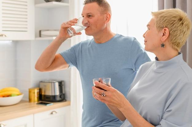Casal de idosos saudáveis a beber água com um copo de água