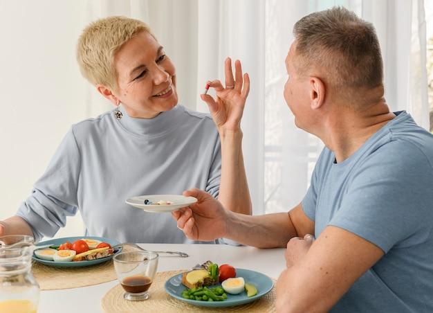 Casal de idosos saudáveis e alegres janta e suplementa a dieta com pílulas de vitaminas