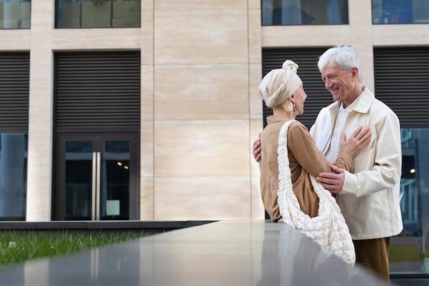 Casal de idosos se abraçando ao ar livre na cidade