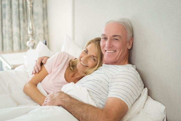 Casal de idosos se abraçando na cama