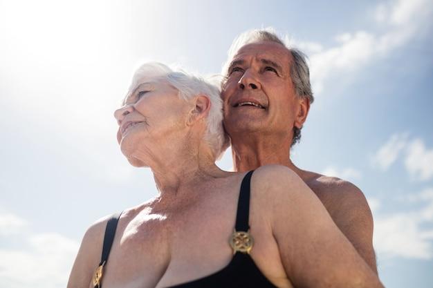 Casal de idosos se abraçando na praia