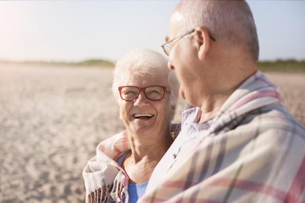 Casal de idosos se aquecendo sob o cobertor na praia