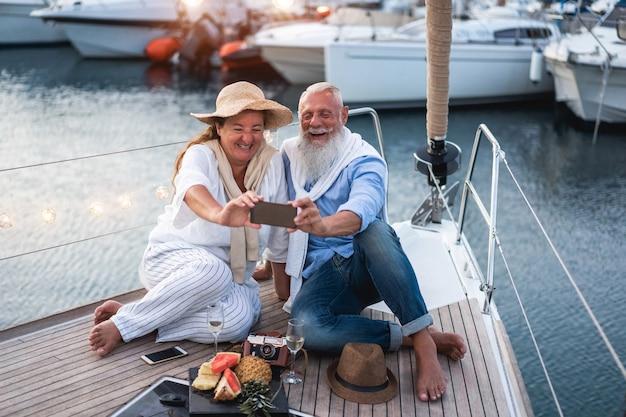 Casal de idosos se divertindo fazendo selfie em um veleiro durante as férias de verão - foco principal no rosto do homem sênior