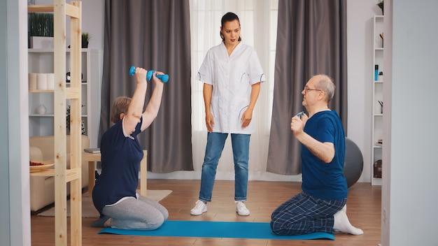Casal de idosos se exercita com a enfermeira durante a reabilitação corporal. assistência domiciliar, fisioterapia, estilo de vida saudável para idoso, treinamento e estilo de vida saudável