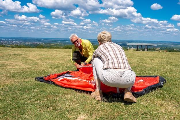 Casal de idosos se preparando para descansar, armando uma barraca