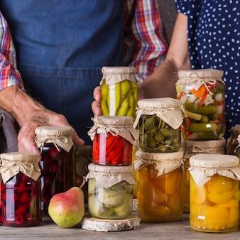 Casal de idosos segurando comida em conserva