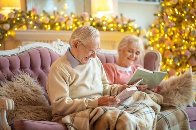Casal de idosos sentado em um sofá lendo livros