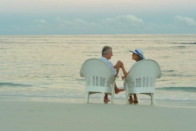 Casal de idosos sentado na praia e olhando um para o outro