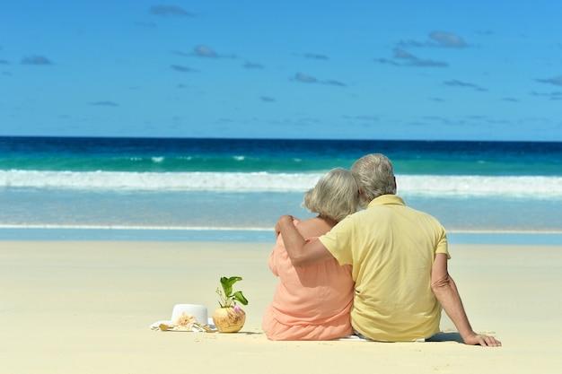Casal de idosos sentado na praia olhando para o mar