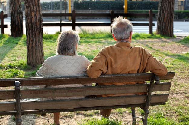 Casal de idosos sentados no banco por trás