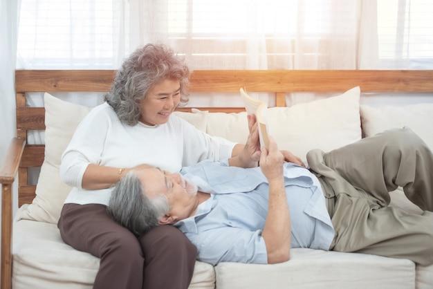 Casal de idosos sente-se no sofá, leia o livro em casa