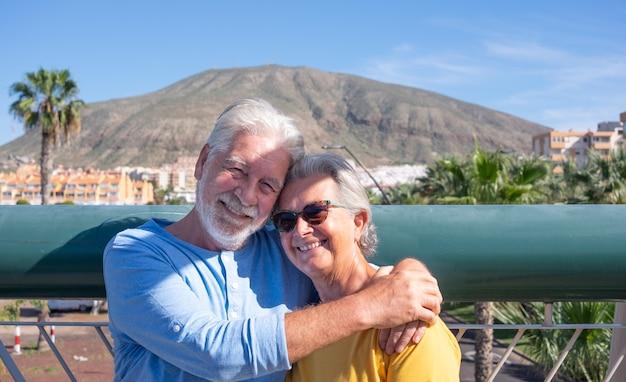 Casal de idosos sorridentes abraçaram-se em uma ponte sobre o tráfego da cidade, olhando para a câmera. aposentados agradáveis e serenos