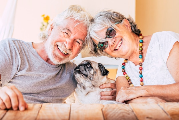 Casal de idosos sorrindo e abraçando um cachorro