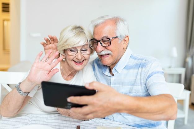 Casal de idosos sorrindo e olhando para o mesmo tablet