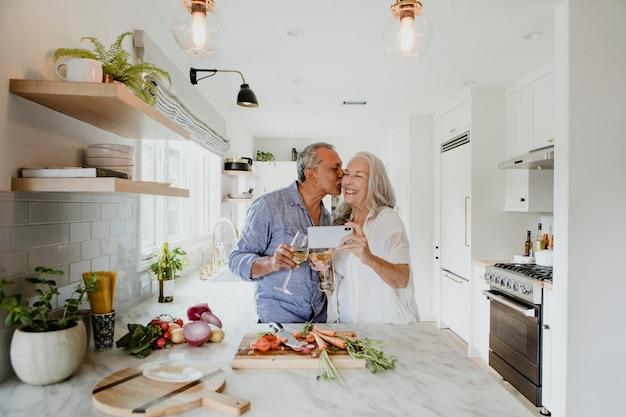 Casal de idosos tirando uma selfie enquanto cozinha em uma cozinha