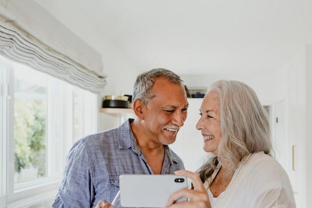 Casal de idosos tirando uma selfie enquanto toma um vinho