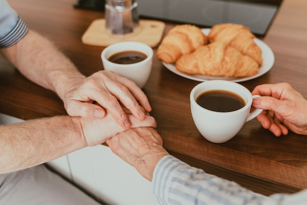 Casal de idosos tomando café da manhã em casa - vida cotidiana de idosos