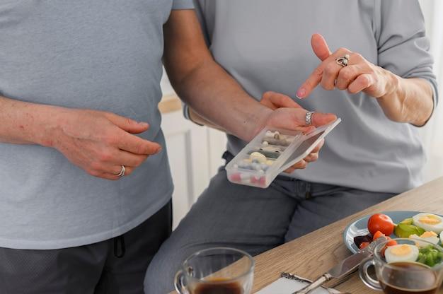 Casal de idosos tomando comprimidos antes do jantar - cuidados de saúde para idosos