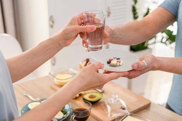 Casal de idosos tomando comprimidos com água antes do café da manhã estilo de vida saudável