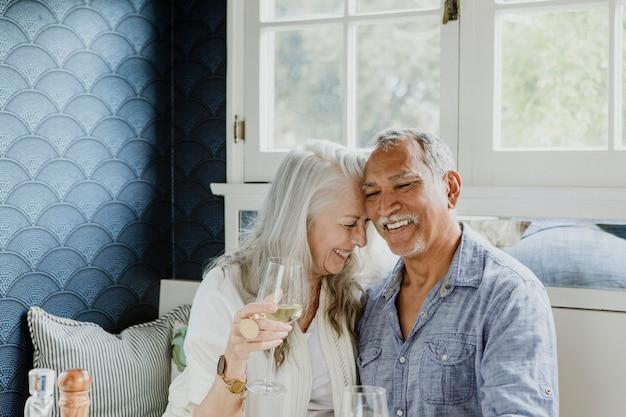 Casal de idosos tomando vinho branco
