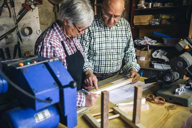 Casal de idosos trabalhando em uma oficina de carpintaria