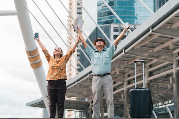 Casal de idosos turistas asiáticos visitando a capital alegremente e se divertindo e olhando o mapa para encontrar lugares para visitar.