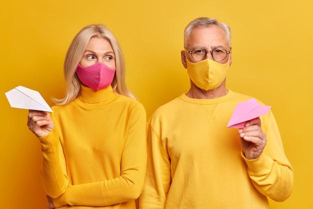 Casal de idosos usa máscaras descartáveis para se proteger da doença do coronavírus e fica em casa durante a quarentena, vestido com roupas amarelas casuais, segurando aviões de papel artesanal em pose no estúdio